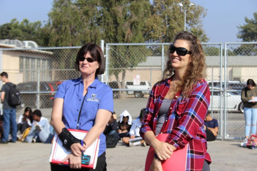 Math teachers Leslie Hicks and Anna Felix laugh during the beginning of the earthquake drill today.