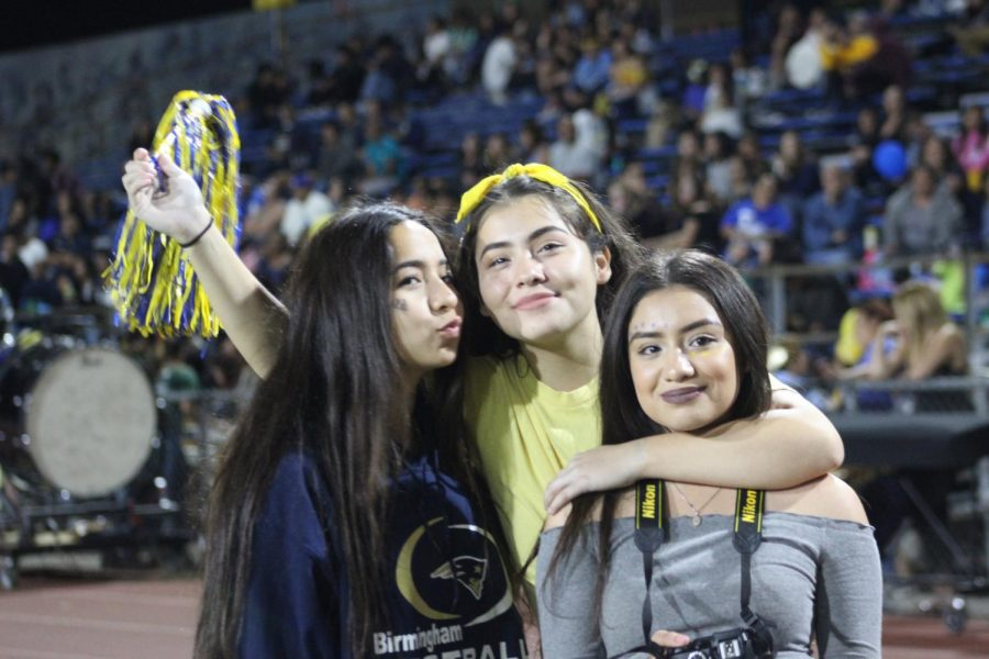Sophomores Ileana Roja, Aimee Guzman and senior Desiree Davila, pose for a picture during the homecoming game on Oct. 27.