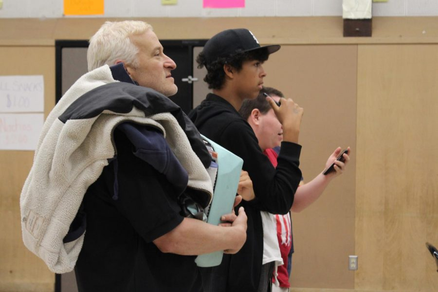 English teacher Ron Baer joins juniors Marcus Rapier and Thomas Short as they watch students enter their answers for a round of Kahoot!.