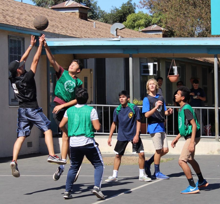 Christopher Gillen and Alberto Serrano compete for the ball in a friendly game of basketball as onlookers stare in anticipation during the House Games on Oct. 16 during lunch.