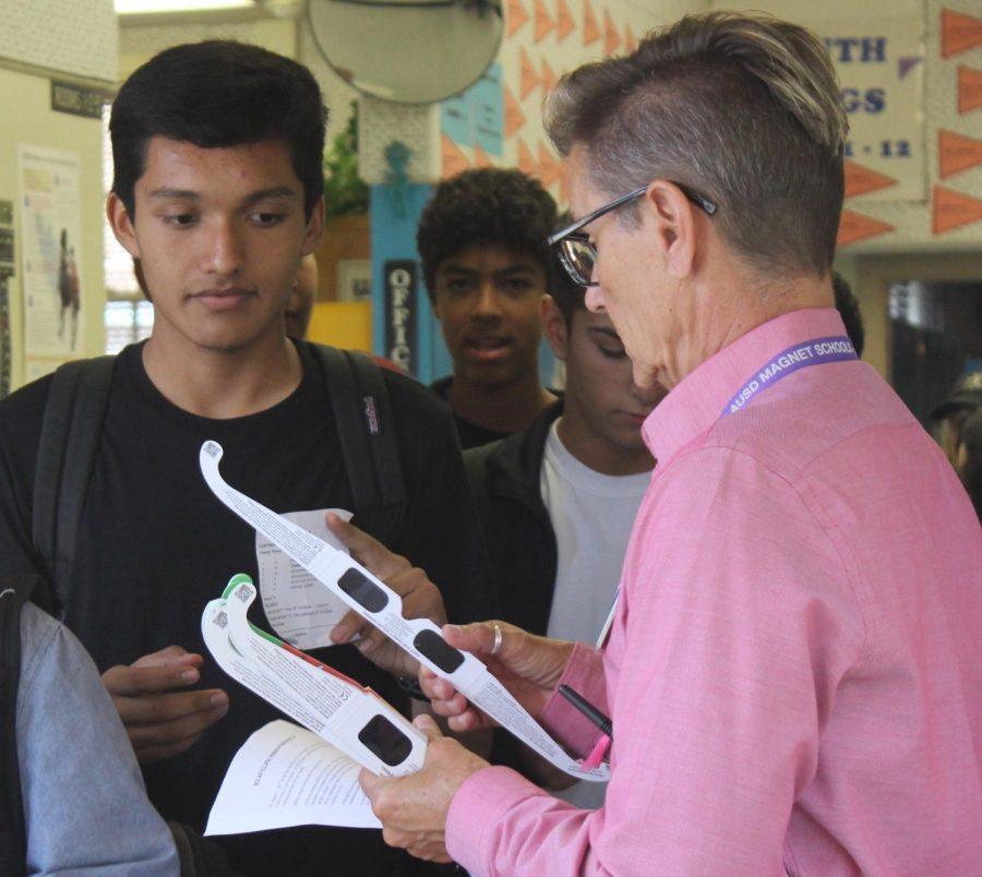 Junior Adrian Contreras receives Eclipse Glasses from Principal Deb Smith on Aug. 21.