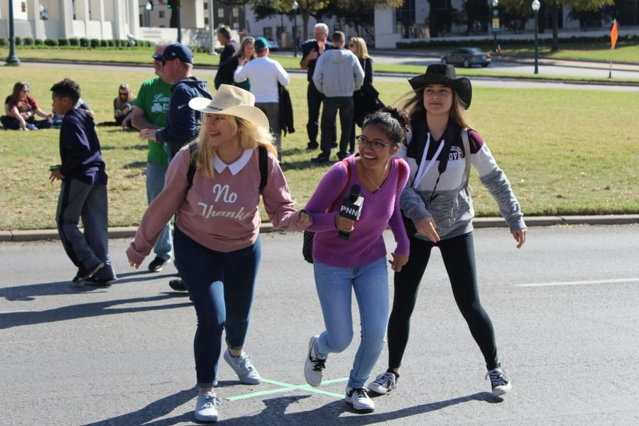 Seniors Sandra Ortega, Nixia Bravo and Nikita Opel run off the street after a group photo on one of the marks depicting the site where JFK was shot.