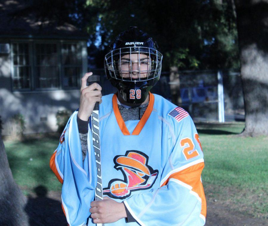 Junior Aaron Garcia poses with his hockey gear.