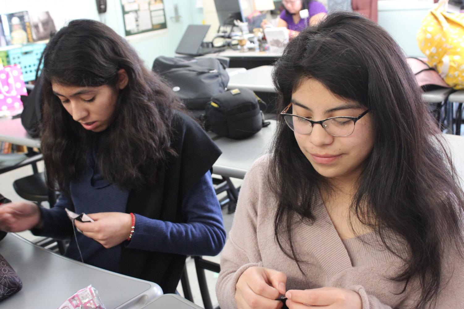 Juniors Vanessa Rizo and Alishon Raymundo practice sewing during the club meeting.