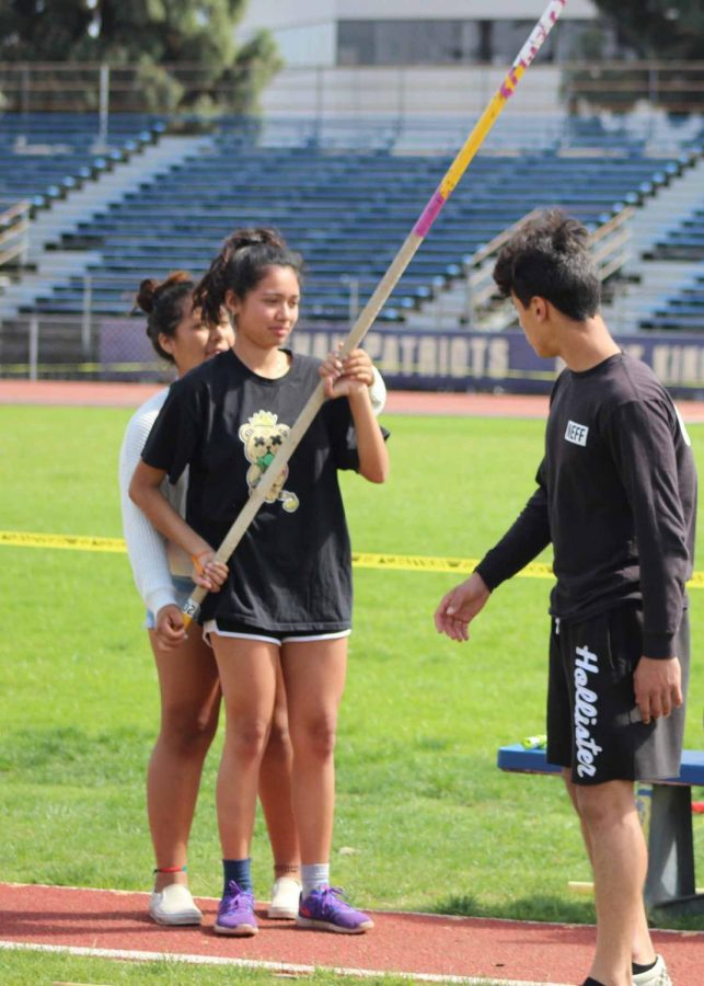 Pole vaulter Nixia Bravo gets help perfecting her form from a teammate