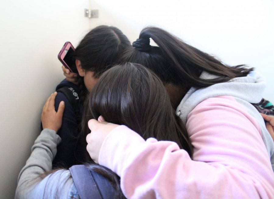 Students huddled in a little circle and held a hushed discussion as they were instructed to be quiet during the active shooter drill today. Students such as these freshmen (Krisia Vasquez, Emily Gaitan and Maribella Ambrocio) tried not to make much noise as they sheltered in place.