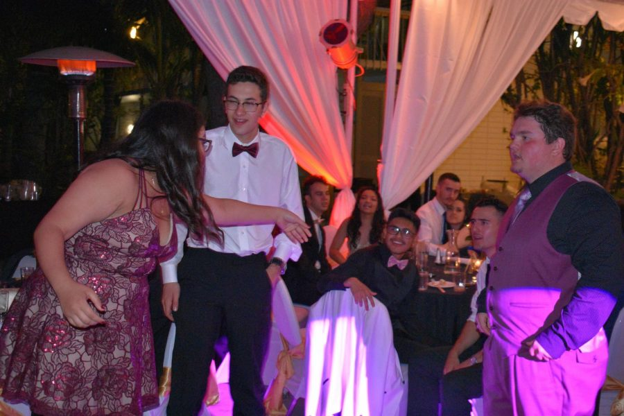A student invites a group of seniors to dance with her at the dance floor during prom.