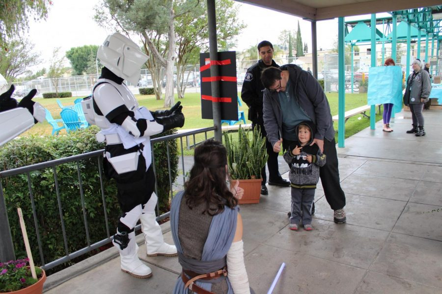 Giving thumbs up to a guest, members of the 501st legion and Rebel Troops wait in front of the school by the Grove to interact with Star Wars fans.