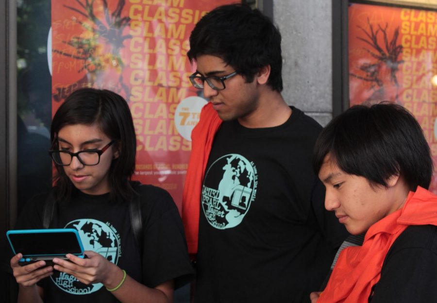 Junior Emely Felix plays on a friend's Nintendo DS as juniors Rudraj Koppikar and Justin Dumindin watch at the Get Lit Classic Slam at the Los Angeles Theater Center on April 26.