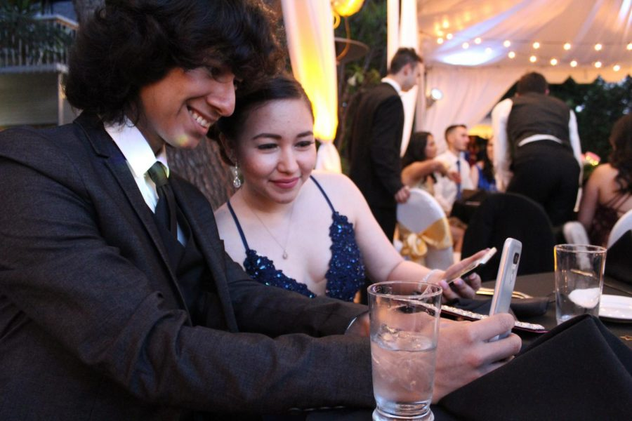 Senior Paola Rivas and her date take a selfie together for their social media accounts at prom.