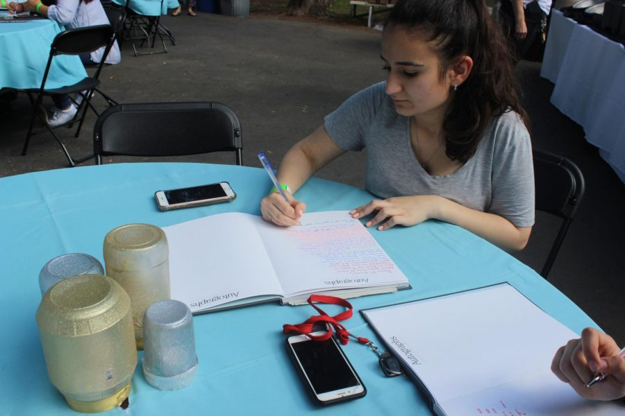 Senior Ruzanna Manvelyan writes a touching message in her friend's yearbook at Senior Sunset on May 31.