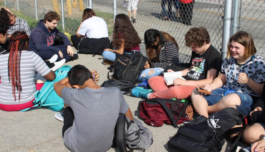 Students in Robert Bryans physical education class entertain themselves by reading books and talking with friends, waiting for the fire drill to end.