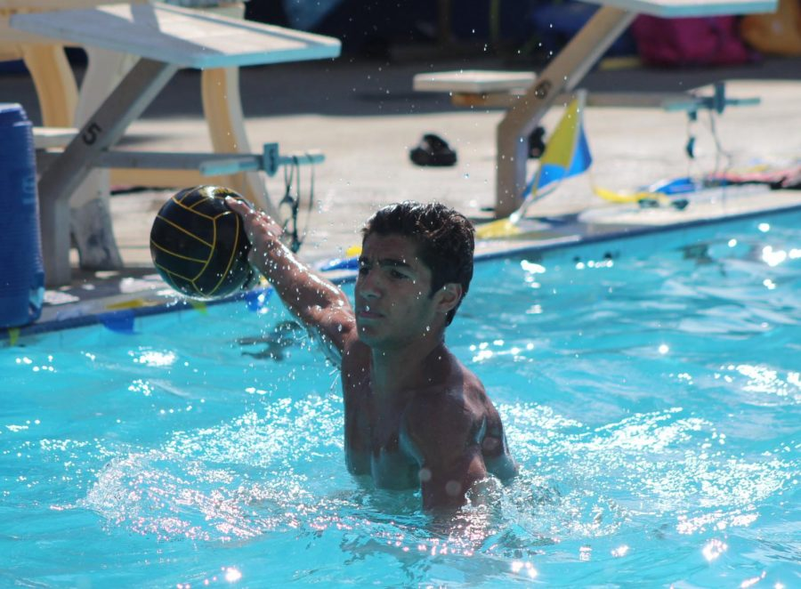 During water polo practice, junior Sepehr Kordbacheh passes the ball to his teammate.