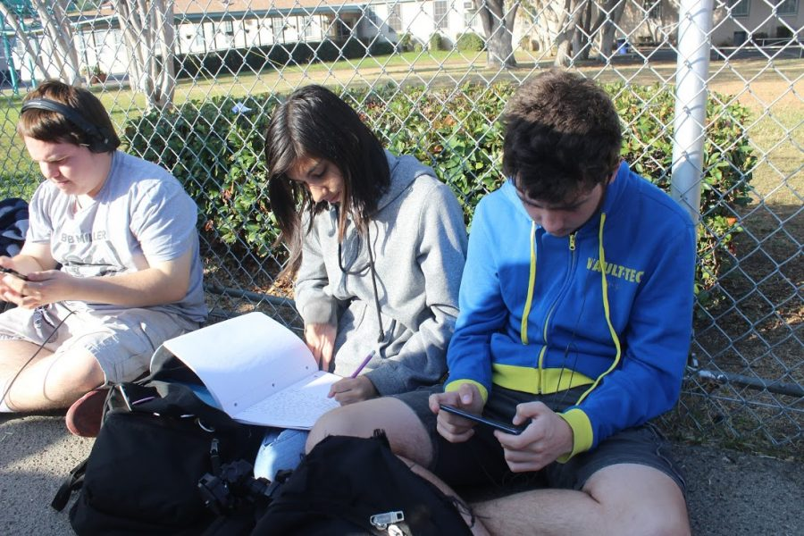 Seniors Thomas Short, Emely Felix and Grantas Jadzevicius play on their phones and do class work during the earthquake drill on Tuesday.