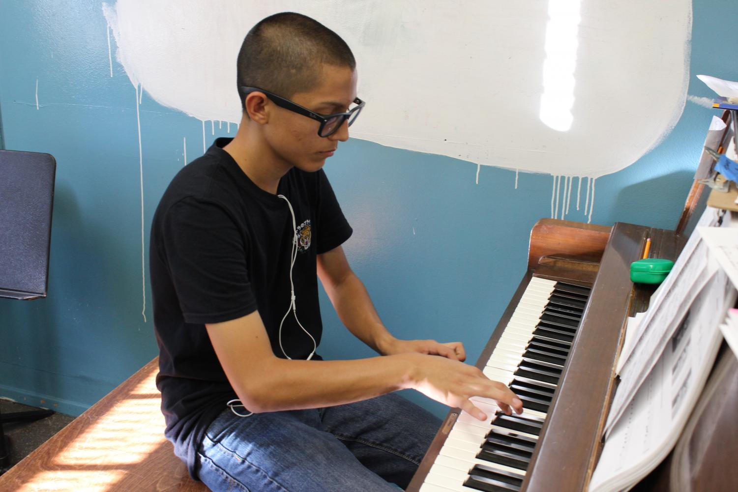 Junior Jason Echeverria plays the piano during practice for Daniel Pearl World Music Day.