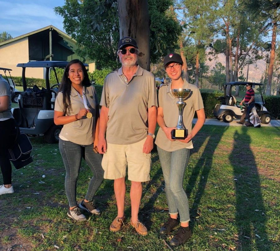 Senior+Astrid+Cabrera%2C+Coach+Kevin+Kelly+and+senior+Lauryn+Uhlenberg+pose+with+their+trophy+after+the+girls+golf+team%27s+final+tournament.