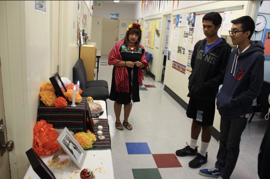 Spanish teacher Glenda Hurtado and juniors Darren Reyes and Andres Prieto check out the Latinx Club's altar for Día de los Muertos on Nov. 2.