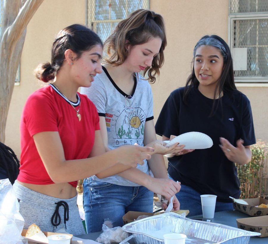 Blanca Larranaga, Hailee Kessler and Joselyn Martinez help serve tamales during the Día de los Muertos celebration in the grove on Nov. 2.