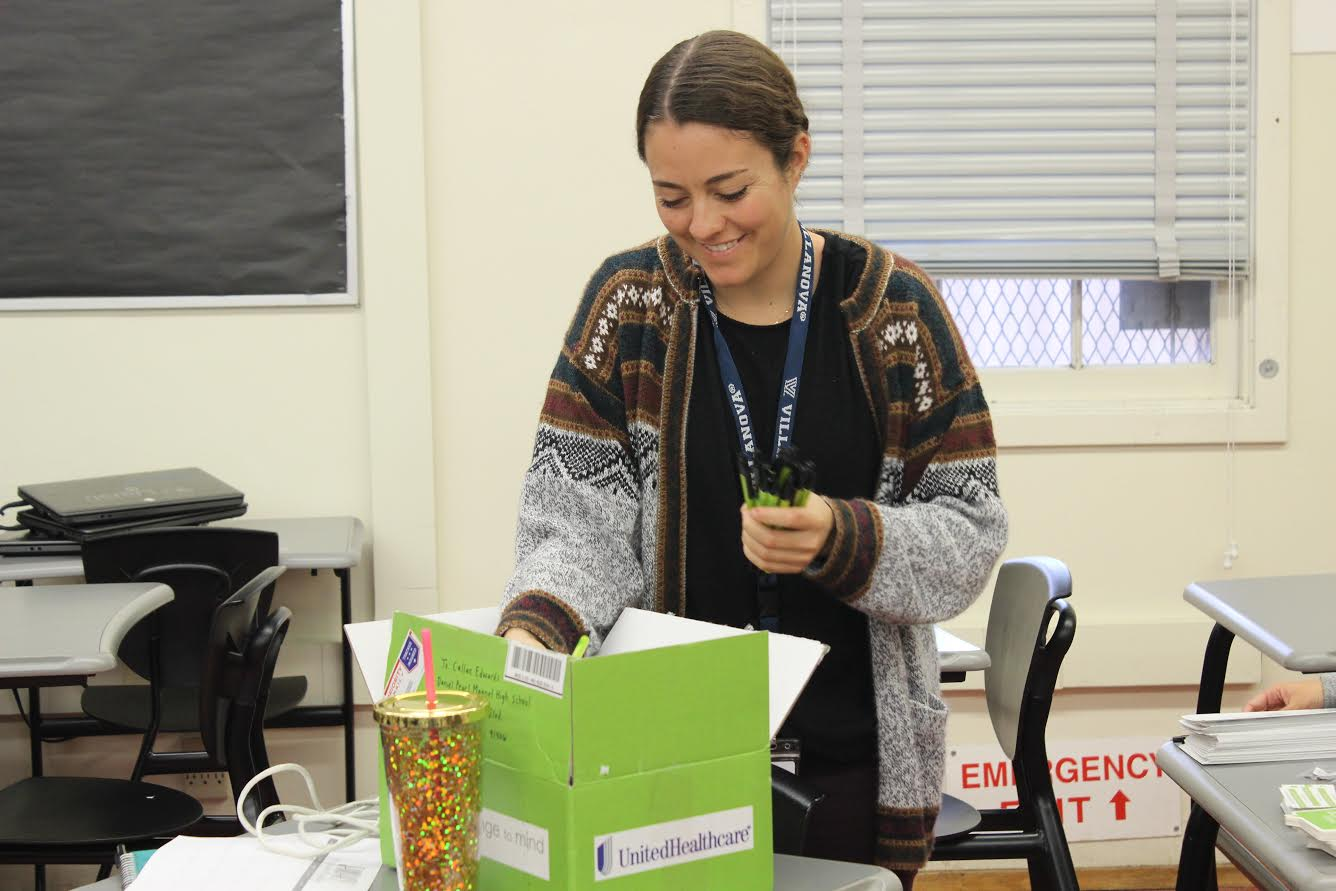 Social work intern and club sponsor Callan Edwards passes out pens to promote the club during a club meeting Dec. 5.