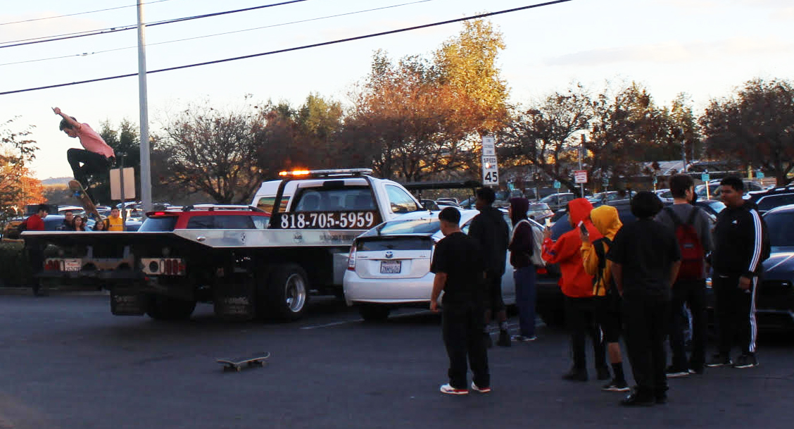 A teenager ollies off the back of a tow truck parked in the plaza while spectators watch and record the stunt.