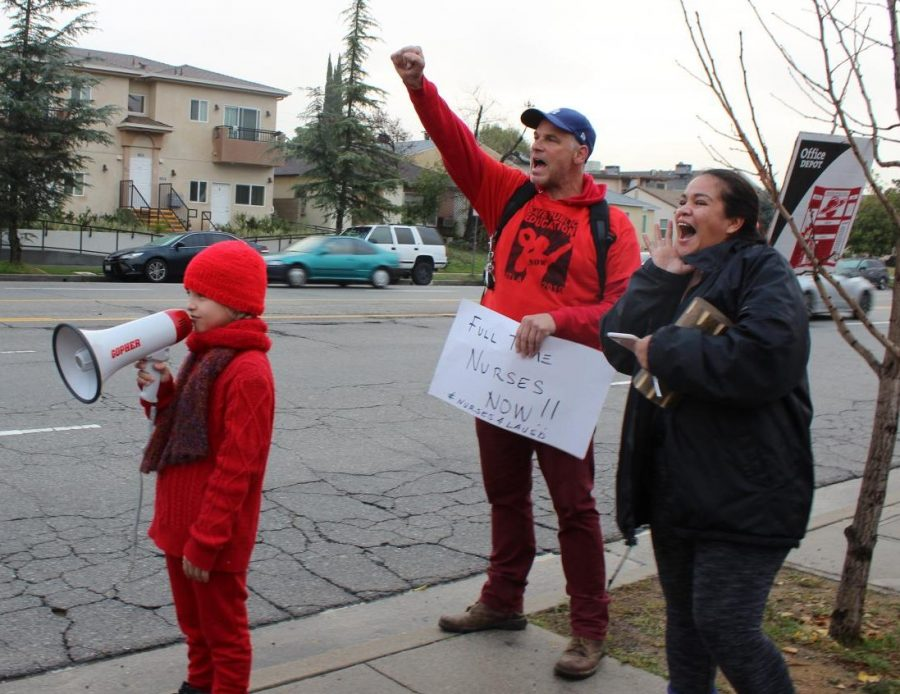 Music teacher Wes Hambright, his son and parent Nadine Freyre chant for more nurses, librarians and teachers outside Daniel Pearl Magnet High School on Jan. 16.