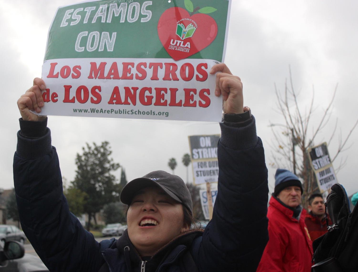 Math teacher Lori Seo proudly holds up a picket sign during the second day of the teacher strike on Jan. 15.
