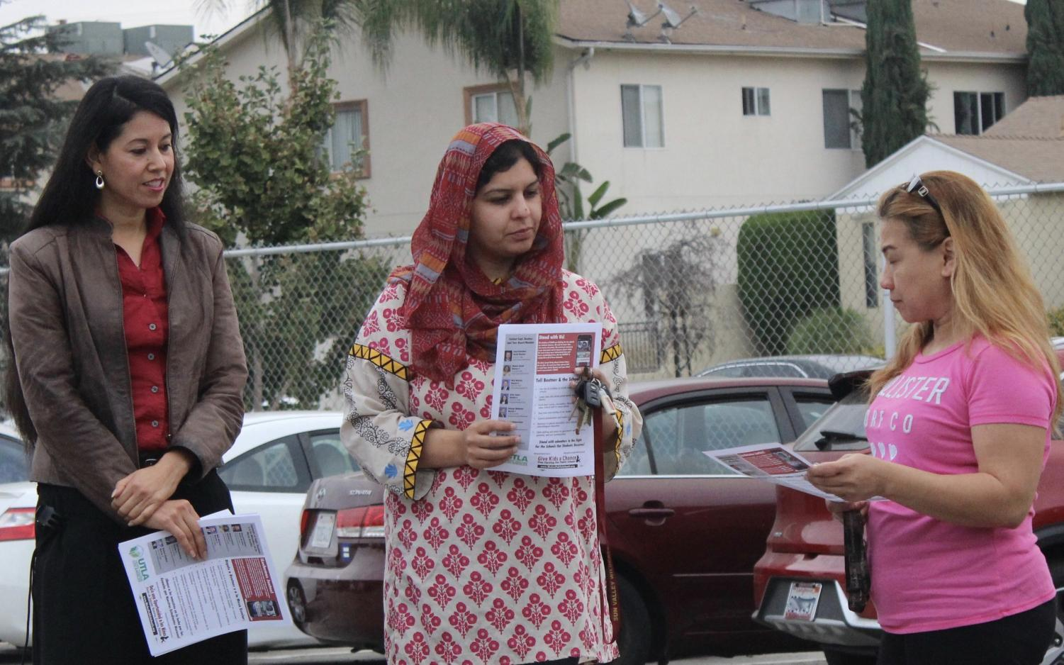 Spanish teacher Marta Rodriguez and resource teacher Sadia Aziz talk with a parent when teachers distributed fliers on union contract negotiations with the school district back in October.
