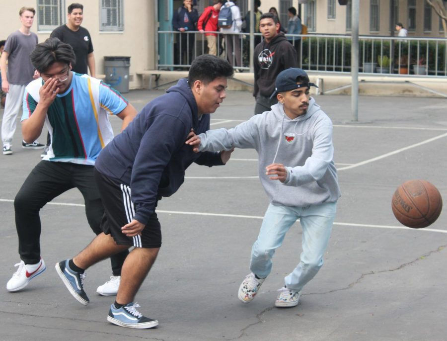 Juniors Joseph Danan, Evan Vargas and sophomore Om Patel go for a loose ball in a basketball game during Fiesta Friday on March 1.