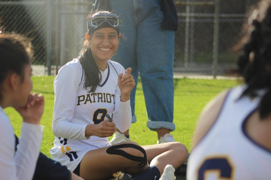 Before the second half against La Cañada High School, junior Maria Ruiz laughs along with Birmingham Community Charter High School's girls lacrosse varsity team during a group discussion.
