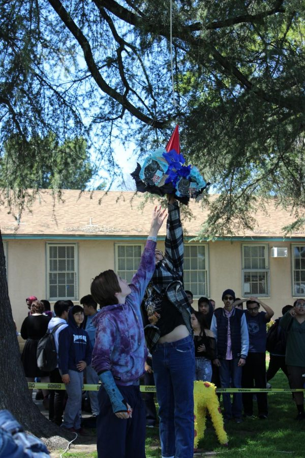 Freshmen Quinn Thorpe and Daniel Husany jump to catch the remnants of a piñata during Fiesta Friday.