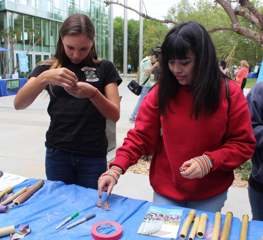Freshman Audrina Murphy and sophomore Krisa Vasquez make flutes out of bamboo from the LA river at the Future Currents: Los Angeles River Festival at California State University Northridge.