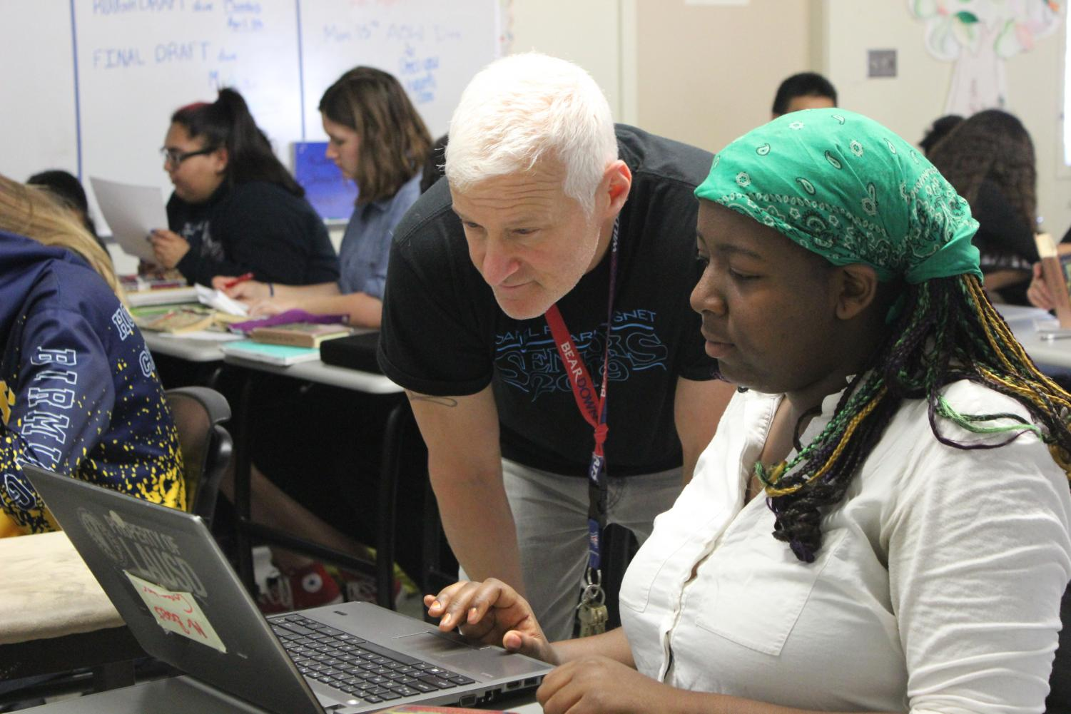 English teacher Ron Baer helps a student with her laptop during period three on April 11.