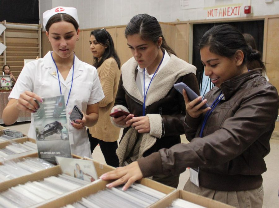 Sophomores Petra Vass, Valery Barrera and Sara Marquez check out the comics sold at a booth in the vendors room during Pearl Con IV on May 11.