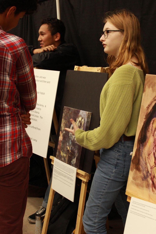 Sophomore+Susannah+Ness+explains+one+of+David+Labkovski%27s+paintings+on+May+9.