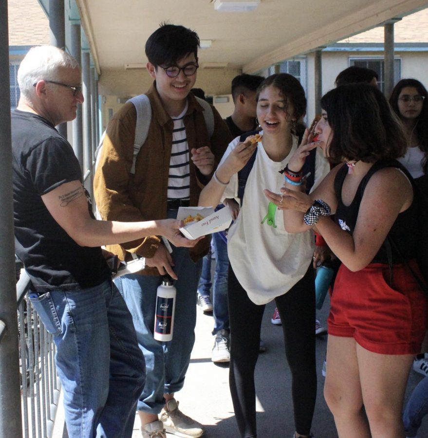 English teacher Ron Baer shares some of his lunch with freshmen Vincent Gillen, Giselle Kalil and Eddy Thelia during Fiesta Friday.