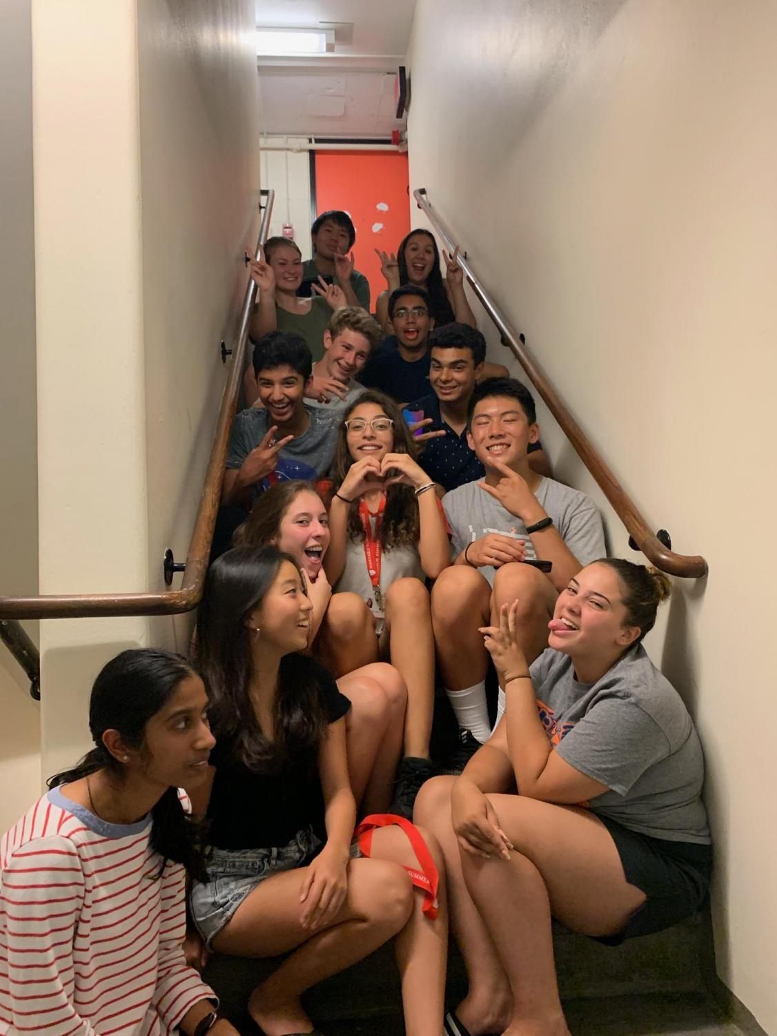 Junior Maria Strake  sits on the steps inside the Leverett House tower with her proctor group on the last day of the program.