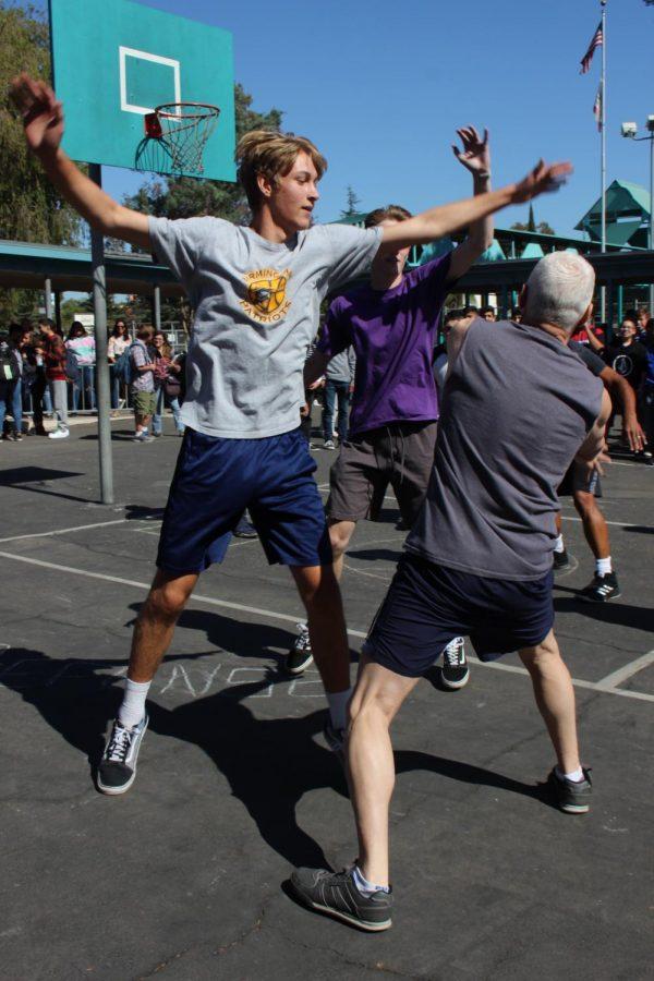 Senior Cuyler Huffman blocks English teacher Ronald Baer from scoring a shot at the teachers vs seniors basketball tournament on Oct. 18.