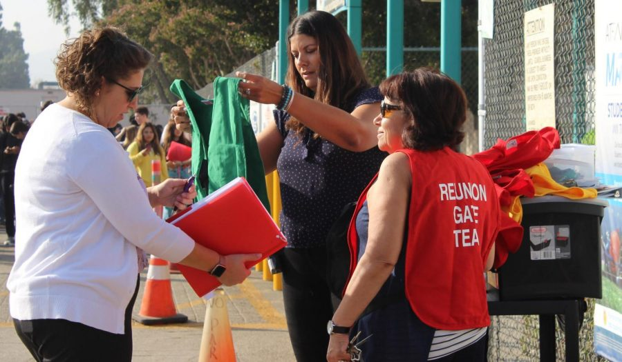 Principal Pia Damonte hands out vests to staff today during the California Great ShakeOut drill during second period.