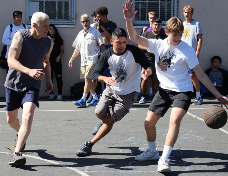 English teacher Ronald Baer and history teacher Fransisco Ortega play against senior Ethan Zinshteyn in the teachers vs senior basketball tournament on Oct. 18.