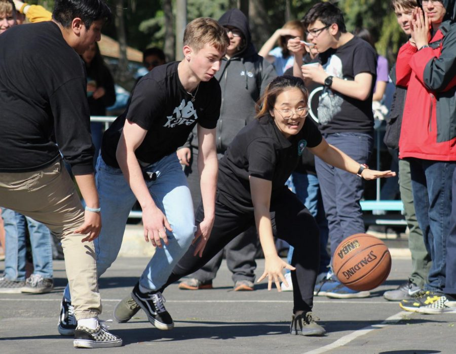 Senior Ethan Zinshteyn moves towards Math teacher Lori Seo to steal the ball. They played during the first teacher sophomore basketball tournament of the year on Feb. 7.