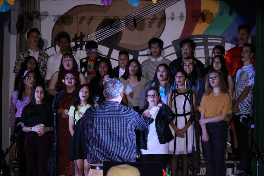 Music teacher West Hambright leads his choir in singing the Star-Spangled Banner on Oct 28.