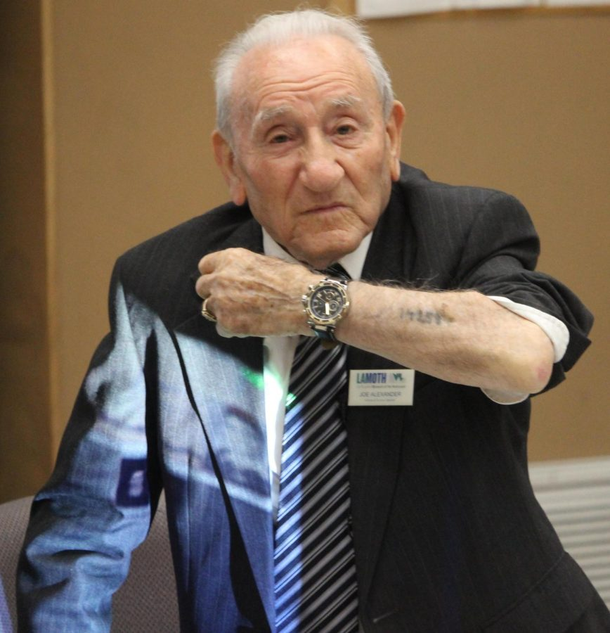 Joseph Alexander shows the tattoo he got during the Holocaust to students on Dec. 6.