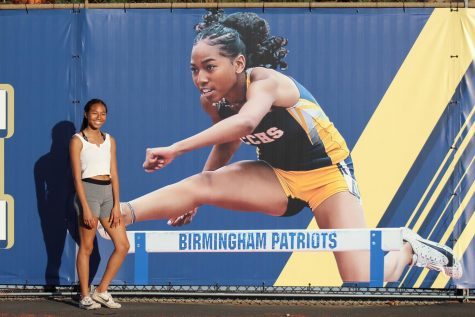 Varsity player Cassia Ramelb smiles next to the new banner across the track field which features her jumping across a hurdle. The junior has been hurdling for Birmingham Community Charter High School track and field team for three years and plans to continue to through college.
