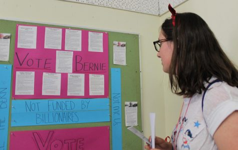 Sophomore Lauren Mills looks at a campaign poster for democratic candidate Bernie Sanders made by history teacher Brenda Helfing's U.S. History class. The mock election was held on March 3 during third and fourth period.