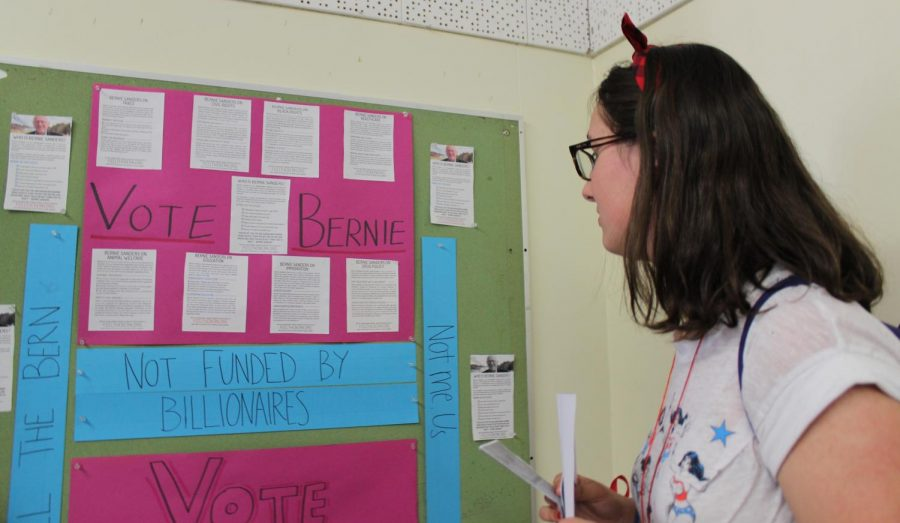 Sophomore Lauren Mills looks at a campaign poster for democratic candidate Bernie Sanders made by history teacher Brenda Helfing
