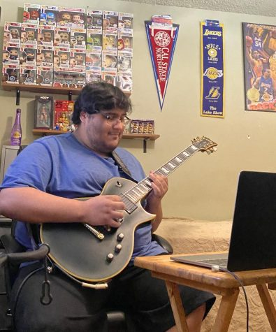 During a Zoom session with DPMHS music students, alumnus Matthew Sarenana plays his guitar.