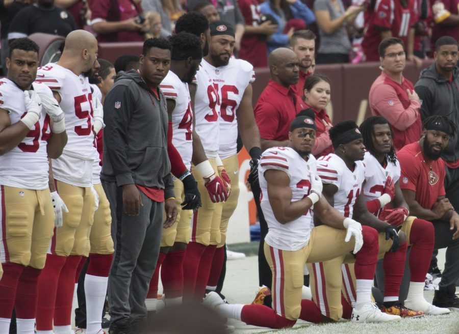 Players from the San Francisco 49ers kneel for the National Anthem in support of their teammate Colin Kaepernick. Kaepernick