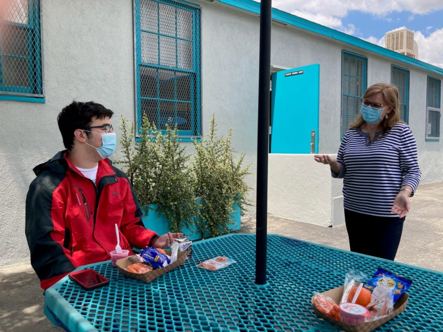 "After more than a year of distance learning, Daniel Pearl Magnet High School reopened for distance learning on Apirl 27. Junior Daniel Husany and parent representative Magaly Ruiz talk during lunch during the first day of hybrid learning on April 27. ""It's weird, seeing people in person,"