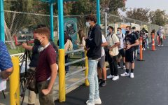 Students wait in line for up to at least 30 minutes to enter campus on the first day of classes on Aug. 16. An overload on the Daily Pass app during the first few days of the new school year made it difficult for students to show that they were cleared to go on campus.