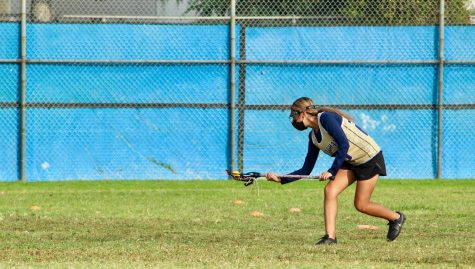 Junior Nancy Medrano hustles to scoop up the ball during a varsity lacrosse practice after school on the field of Birmingham Community Charter High School. Due to COVID protocols, student athletes have to take several precautions such as wearing masks on the field during practices and games.